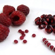 Red chalcedony beads next to raspberries and pomegranate seeds