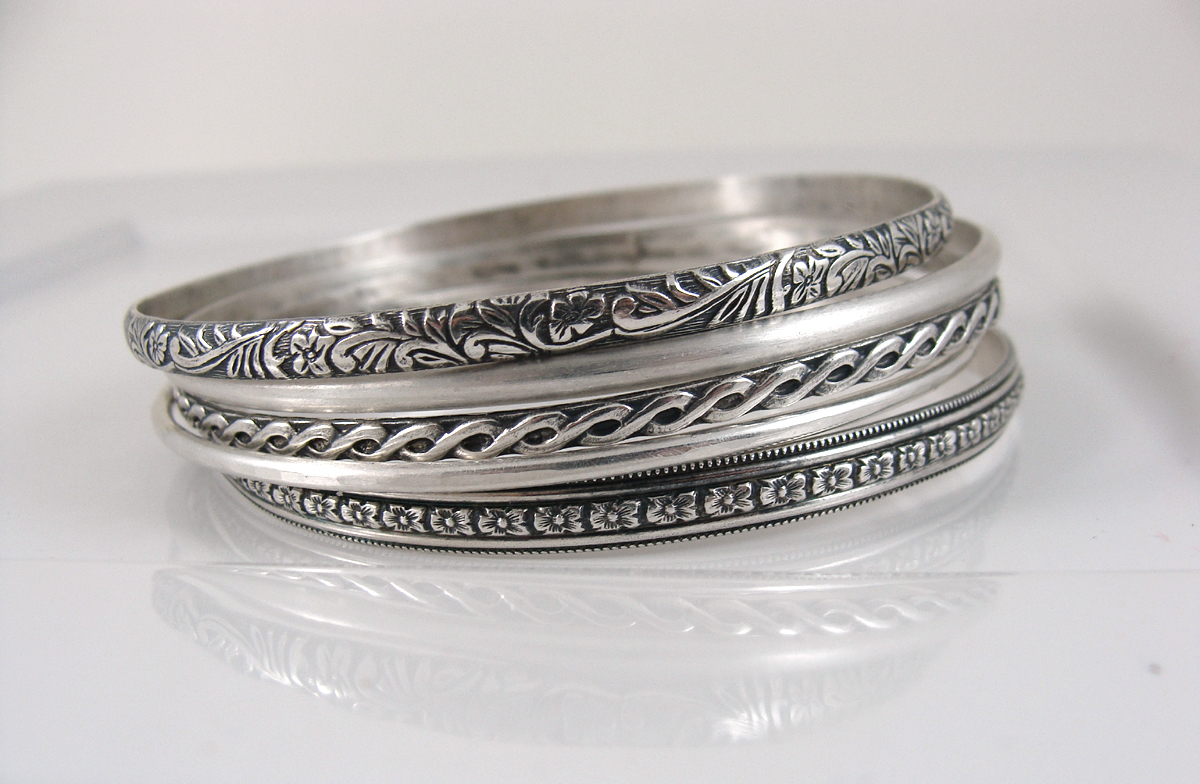 a variety of sterling silver patterned bangles
