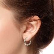close up of small hoop earrings on model